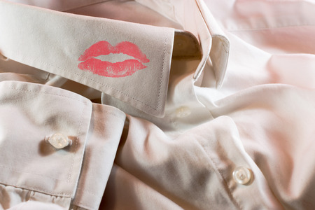 Close-up of a mans white business shirt with a smudge of a womans bright red lipstick on the collar