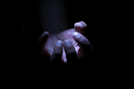 clutching: White male hand in darkness and shadow clutching an invisible empty item Stock Photo