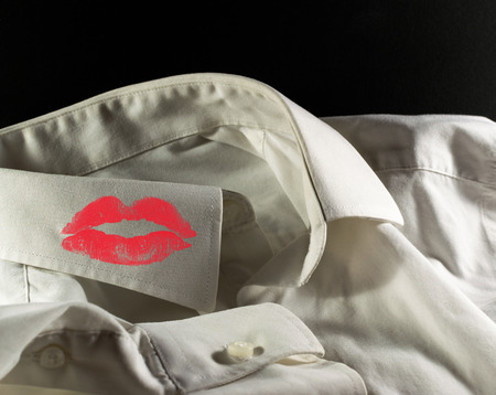cheater: White used shirt on a black background with womans red lipstick on the collar