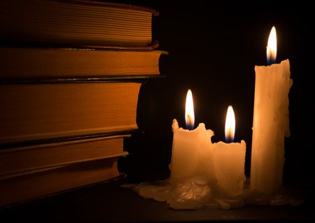 ancient books: Three white candles lighting ancient books during the darkness of night time Stock Photo