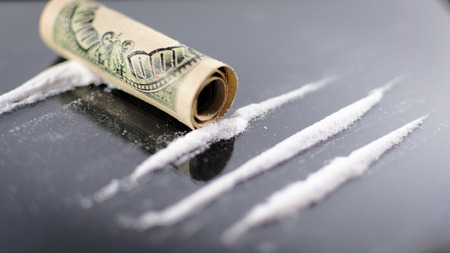 one hundred dollar bill: Lines of cocaine on a glass surface with a rolled up one hundred dollar bill