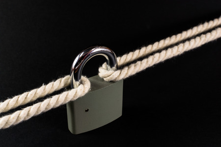 breaking the code: Locked padlock secures two separate ropes together under tension Stock Photo