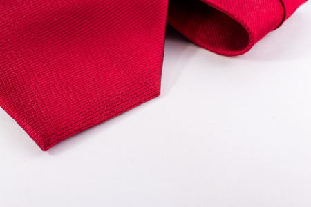 tie necktie: Closeup of a smooth red silk tie belonging to a modern business man on a white horizontal background