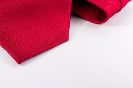 lazo regalo: Primer plano de una corbata de seda roja lisa que pertenece a un hombre de negocios moderno en un fondo blanco horizontal Foto de archivo