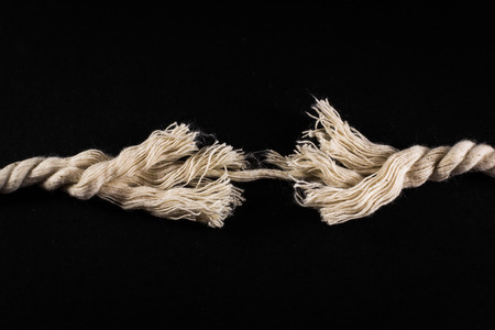 frayed: Cut rope with loose frayed strands keeping the white rope from snapping