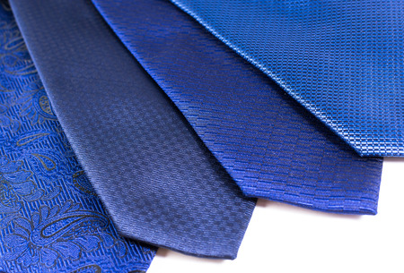 untied: Four blue silk ties in a display row belonging to a modern business man on a white background Stock Photo