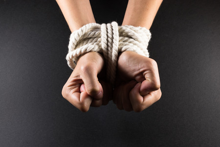 White female hands in bondage tied up with white rope