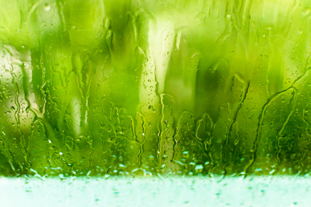 run down: Rain droplets run down a window during a rainstorm as green trees sway in the background