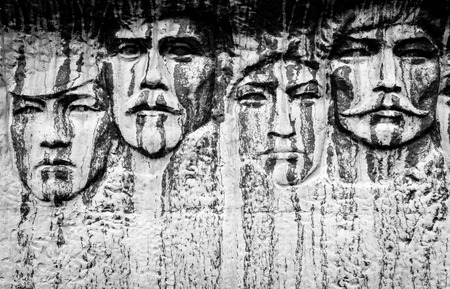 weatherworn: Stone carved faces on white marble rock with signs of aging Stock Photo