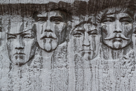 weatherworn: Stone carved faces on white marble rock