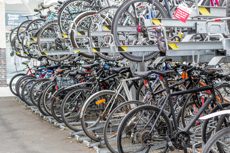 parked bikes: Many commuter bikes parked and locked outside a train station in Chelmsford Essex in August 2015 provide ecological friendly transport for passengers Editorial
