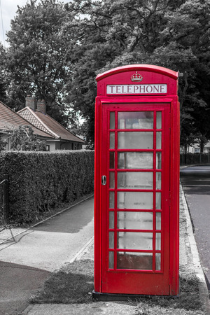 phonebox: Single British red telephone box or booth against a blue summer sky in a suburban location