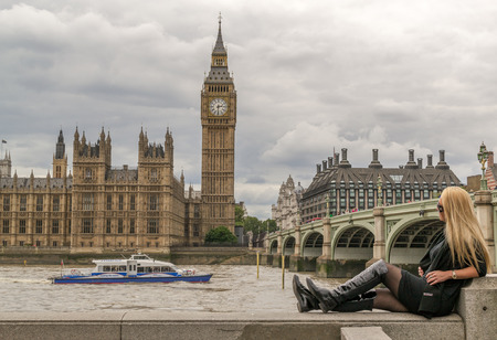 blond haired: August 18th - Blond haired beautiful woman poses whilst looking at Big Ben and the Houses of Parliament in London as a speedboat races past