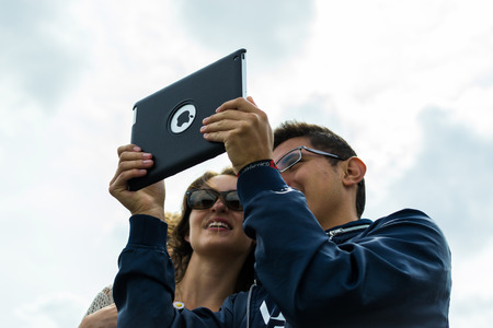 tourists stop: London 18th of August 2015 - Two European Tourists stop to take a selfie using their new Apple iPad in London in August 2015