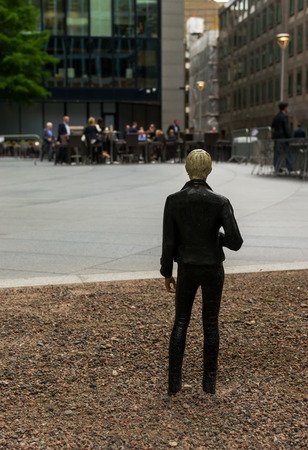 carson city: August 18th 2015 - Miniature human figure looks at city workers as part of an Art installation by Japanese artist Tomoaki Suzuki for Sculpture in the City August 2015