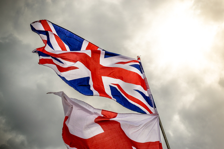 britannia: English Union Jack and saint George flag flapping in the wind against a grey cloudy sky