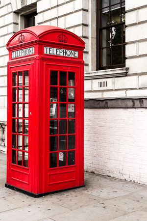 antique booth: Single red telephone booth in London in bright red paint and with desaturated colors with no people