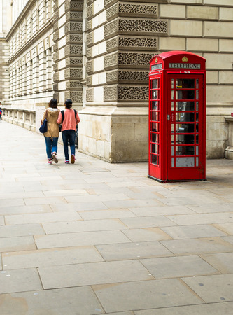 desaturated colors: Single red telephone booth in London in bright red paint and with desaturated colors with two unidentified tourists walking past