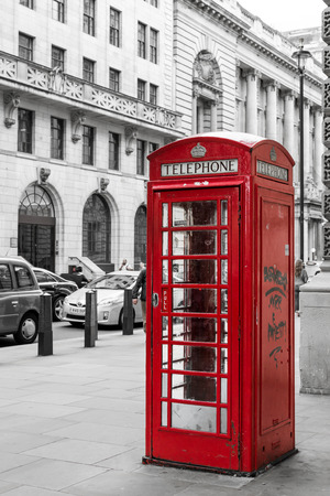 desaturated colors: Single red telephone booth in London in bright red paint and with desaturated colors with no people