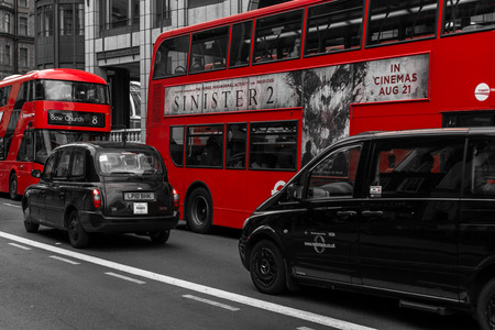 desaturated colors: Modern red buses and back cabs in motion on Bishopsgate Road in London during the summer of August 2015 with desaturated colors Editorial