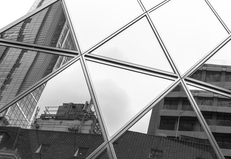 triangle shaped: Triangle shaped abstract from window reflections of a modern office building against a clear white sky