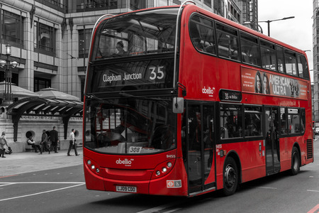 desaturated colors: Modern red bus in motion on Bishopsgate Road in London during the summer of August 2015 with desaturated colors Editorial