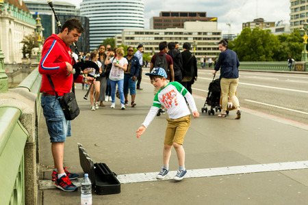 busker: 18th of August - Busker plays the Westminster bridge near big ben as a happy caring child throws coins into his case