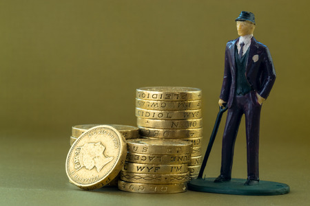 coins: Single classical businessman miniature toy in suit and tie on a golden background with copy space surrounded by English one pound coins