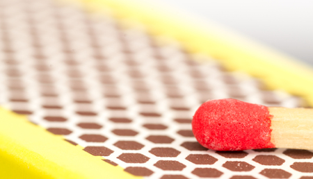 striking: Studio macro close up of a red match head about to strike the honeycomb shaped rough striking surface of a matchbox