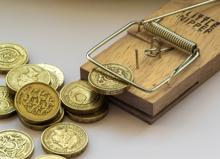 await: Single mousetrap in macro on a white background catches and traps a British pound coin as other coins await their turn