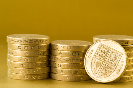pile of coins: Three piles of English pound coins set against a golden background Stock Photo