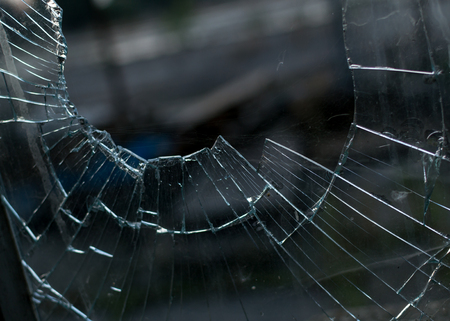 disturbing: Closeup shot of a smashed broken glass window pane with a very blurred background and a disturbing viewing angle Stock Photo
