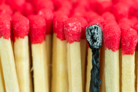 burned out: Studio macro close up of red headed match sticks standing upright with one single isolated burnt black match Stock Photo
