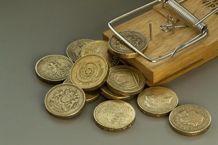 await: Single mousetrap in macro on a grey background catches and traps a British pound coin as other coins await their turn