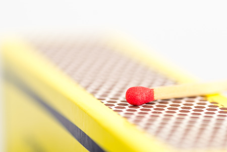 match head: Studio macro close up of a red match head about to strike the honeycomb shaped rough striking surface of a matchbox