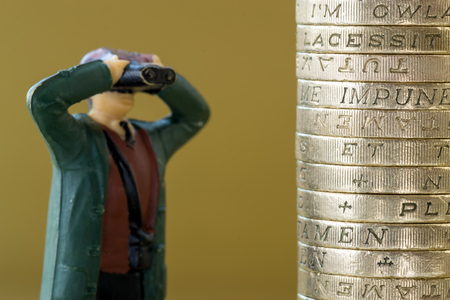 money pound: Single miniature model looks through binoculars into a pile of British pound coins