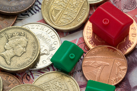 differing: Imitation model red and green plastic houses with chimneys rest on top of British coins and notes of differing values and colors