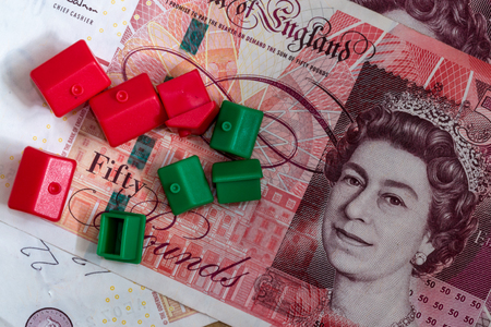 home finances: Imitation model red and green plastic houses with chimneys rest on top of English fifty and twenty pound notes