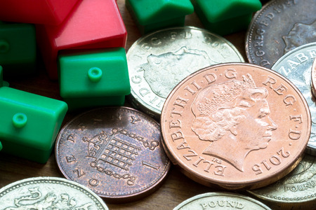 home finances: Imitation model red and green plastic houses with chimneys rest on top of British coins of differing values and colors