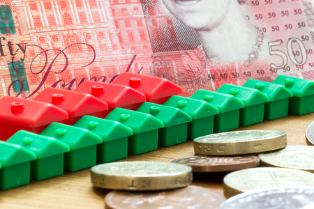 monopoly money: Green and red imitation plastic model houses form a dynamic diagonal row with a single British fifty pound bank note in the background and English pound coins in the foreground
