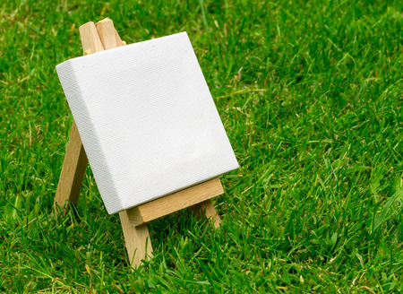artists model: Close up of a wooden miniature model artists easel on grass with copyspace area and design space Stock Photo