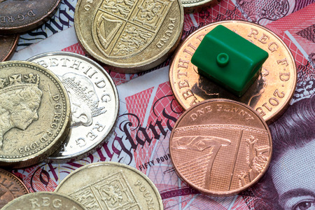 differing: Imitation model green plastic house with a roof rests on top of British coins of differing values and colors and a fifty pound note