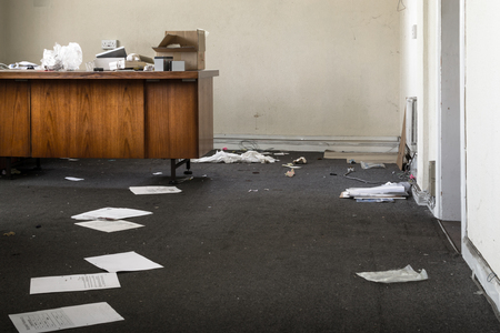 Abandoned Office with strewn discarded papers and rubbish on old wooden desks