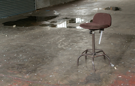 broken chair: Solitary broken office chair stands in a deserted and forgotten factory
