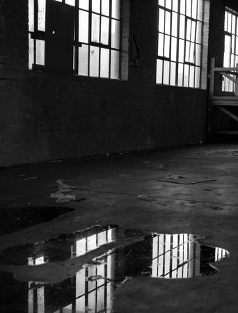 murky: Pools of rain water gather into puddles of murky water reflecting smeared windows in a forgotten abandoned factory Stock Photo