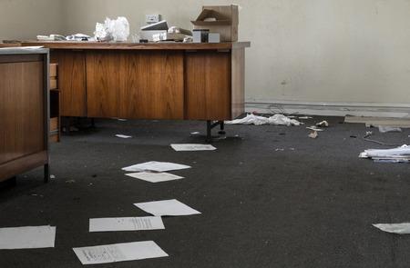 오래 된 목조 책상에 흩어져있는 폐기 된 종이와 쓰레기가있는 버려진 사무실 스톡 콘텐츠