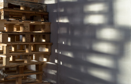 euro pallet: Single stack of many wooden storage packing pallets casting a shadow on a white factory wall
