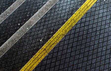 providing: Yellow and white stripped anti-slip pedestrian steps with diagonal patterns providing safety and protection for workers