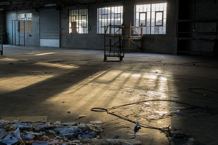 empty warehouse: Empty abandoned deserted factory warehouse with sunlight filtering through derelict broken windows
