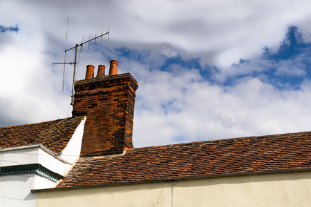 redstone: Traditional brickwork redstone chimney set upon a red tile roof in a residential backdrop Stock Photo